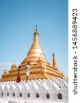Sanda Muni Paya Mandalay Myanmar, young couple on vacation in Myanmar walking by temple, golden white temple at Mandalay