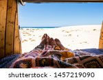 Couple of traveler feet love and live together the travel wanderlust lifestyle in alternative summer vacation with old wooden vintage van - coloured blancket and sea and beach view from camper bed - stock photo