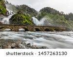 Latefoss twin waterfalls streams under the stone bridge archs, Odda, Hordaland county, Norway