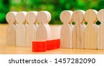 Small photo of The red figure of a man falls out of the line of people. Concept of employee dismissal and personnel management in a business team. Weak link. Staff toxicity. Bad worker. Demote. Fired Selective focus