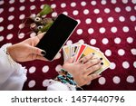 Small photo of Fortune teller reading fortune lines on screen smartphone modern horoscopes online fortune telling application Palmistry Psychic readings and clairvoyance hands concept with Tarot cards divination