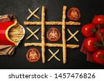 Small photo of Game of tic tac toe of french fries and tomatoes. Choosing healthy vs unhealthy foods. Fit or fat concept.
