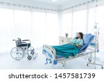 Small photo of Inattentive young Asian female patient with hospital clothes feels unhappy, bad, sad . She is thinking about medical diagnosis, surgery and treatment on hospital bed in white room, hospital.