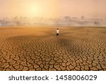 Small photo of a man standing at empty land of dry cracked earth and looking to the big city with air polluted environment metaphor Climate change, Water crisis, Environment pollution of activity from urban concept.