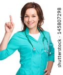 Portrait of a young attractive woman wearing doctor uniform and pointing up with forefinger, isolated over white - stock photo