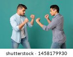 Small photo of Primitive Instincts And Male Behavior. Strong Arab Guys Posing With Clenched Fists Preparing For Fight On Turquoise Studio Background