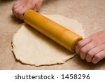 hands roll out dough - stock photo