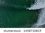 An aerial view of a surfer riding a wave in the tropical turquoise waters of Noosa Heads. The waters are bay with other surfers on a variety of boards. A popular surf spot on the Queensland coast
