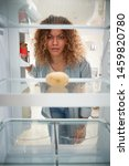 Small photo of Disappointed Woman Looking Inside Refrigerator Empty Except For Potato On Shelf