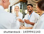 Stock photo young african medicine student welcomes senior doctor with handshake in coffee break 1459941143