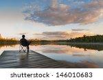 Man Sitting On A Lake Pier At...