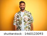 Stock photo young indian man on vacation wearing summer floral shirt over isolated yellow background with a 1460123093