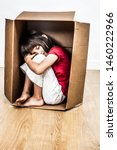 Stock photo concept of sad crying tired little child hunched in a small cardboard box seeking for protection 1460222966