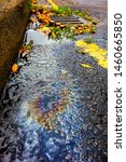 Small photo of Spilt Petrol Gasoline Oil Running Down a Drain On a Road Gutter Environmental Pollution