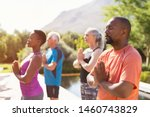 Small photo of Four senior people meditating with joined hands and closed eyes breath deeply. Multiethnic class of mature people doing meditation with joined hands and relaxing together at park.