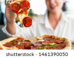 Small photo of Young attractive smiling woman eating pizza at street cafe. Cheat meal. Cheat day