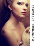 Portrait of a beautiful young woman undressed holding luxurious fur coat after ball. Arty make-up of golden foil. Femme fatale. Vintage (old hollywood) style. Healthy skin. Close up. Studio shot - stock photo