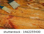 Small photo of Wooden floor renovation - Scrape tool and brush placed on floor with paint scraped