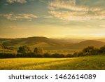 Sunset Over Hilly Landscape ...