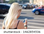 Small photo of The girl crosses the road in the city at a pedestrian crossing and looks into the phone. Young blonde woman is using smartphone while standing at a crosswalk. Inattentive female focused on the phone