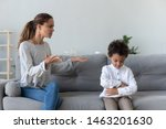 Small photo of Annoyed serious mom scolding lecturing stubborn african kid son for bad behavior at home, angry parent mother punish little mixed race guilty child boy demand discipline, family conflicts concept