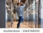 Small photo of Overjoyed funny young business man jumping in hallway celebrate success victory win reward, happy excited male employee rejoice promotion work well done on friday yes gesture dancing alone in office