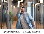 Small photo of Ecstatic excited male winner dancing in office hallway laughing celebrating work achievement professional win, happy overjoyed business man enjoy victory dance euphoric about success reward promotion