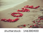 Small photo of Caption word love in the sand of the sea. Love inscription from the petals of roses.