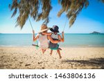 Small photo of Boys swinging on log swing at Dingo Beach, near Airlie Beach in the Whitsundays, Queensland Australia. Tropical holiday fun with kids in paradise.