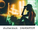 Small photo of Hip-hop girl in cap in neon light. Fashion portrait of modern young woman in cap and sunglasses.