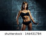 Young sports woman on wall background. - stock photo