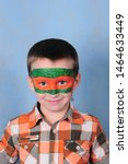 A Boy With A Painted Face With...