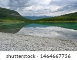 pebble beach and calm lake in Norwegian mountains - stock photo