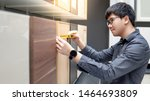 Stock photo asian man using tape measure on cabinet panel choosing materials or countertops for built in 1464693809