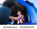Truck driver occupation. Professional middle aged trucker in cabin driving truck and smiling. Transportation industry. - stock photo