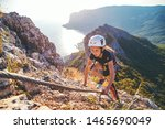 Kid girl of 10 years old in helmet and special safety device equipment climbing high mountain via ferrata. Crimea.