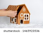 Small photo of The hand-made eatable gingerbread house, adding by hand of part of roof and snow decoration