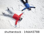 Couple Lying On Snow Making...