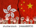 Small photo of Rise up hand with China and Hong kong flags print screen on wall cracked.Hong kong people protestor concept.