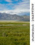 Small photo of Long green valley next to Lake Crowley, Mono County, California. USA. Green wetland with mountain on the background during clouded summer.