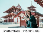 Stock photo asian tourist woman looking paper map at ancient of pagoda temple japanese architecture osaka japan 1467043433