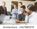 Small photo of A team of young businessmen working and communicating together in an office. Corporate businessteam and manager in a meeting.