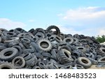Small photo of Industrial landfill for the processing of waste tires and rubber tyres. Pile of old tires and wheels for rubber recycling. Tyre dump
