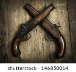 Two vintage pistols on wooden background - stock photo