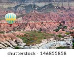 View of the air balloon flying over multicolored rock formations of Cappadocia, Turkey  - stock photo