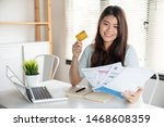 Small photo of Happy asian young woman smiling holding so many expenses bills such as electricity bill, water bill,internet bill and cell phone bill with easy life to payment credit card on her hand