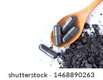 Small photo of Natural black wood charcoal and activated charcoal capsules in wooden spoon isolated on white background. Medical tablet, Absorbent carbon,emergency for toxin removal concept.Top view. Flat lay.