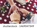 Small photo of Fortune teller reading fortune lines on hand Palmistry Psychic readings and clairvoyance hands concept with Tarot cards divination / Palm reading