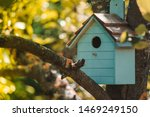 Wooden blue birdhouse on a...