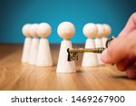 Small photo of Coach unlock potential - motivation concept. Coach (manager, mentor, HR specialist) unlock leader potential and talent represented by wooden figurine and hand with key.